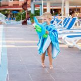 Beautiful child plays with balloons at the edge of the pool stock photo