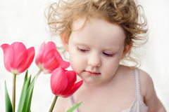 Beautiful child and red tulips. Royalty Free Stock Photo