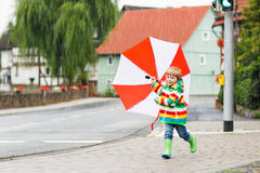 Beautiful child with red umbrella and colorful jacket outdoors a Stock Photos