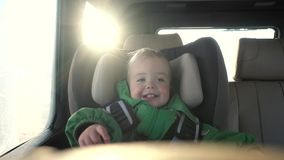 A happy child is traveling in the car. A beautiful child is riding in a car seat in a solar car stock video