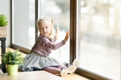 A beautiful child is sitting near a large window. A little girl, 4-5 years old, is sitting  the windowsill of a large window in a cafe royalty free stock photography