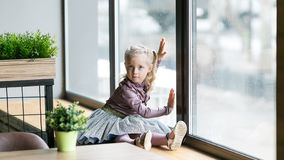 A beautiful child is sitting near a large window. A little girl, 4-5 years old, is sitting on windowsill of a large window in a cafe stock images