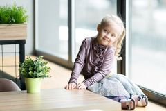 A beautiful child is sitting near a large window. A little girl 4-5 years old, is sitting on the windowsill of a large window in a cafe stock images