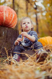 Beautiful child sitting playing with a straw. Royalty Free Stock Photography