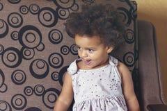 Beautiful child sitting on sofa royalty free stock image