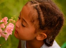 Free Beautiful Child Smelling Flowers, Green Background Royalty Free Stock Image - 217032306