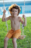 Beautiful child in swing. Holidays of summer royalty free stock photography
