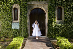 Beautiful child in white dress outside chapel. Beautiful child wearing white dress standing outside chapel door Stock Image
