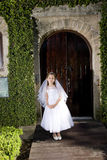 Beautiful child in white dress outside chapel door Royalty Free Stock Photo