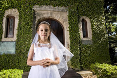Beautiful child in white dress outside chapel door. Beautiful child wearing white dress standing outside chapel door Royalty Free Stock Image