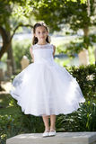 Beautiful child in white dress on park bench. Beautiful child wearing formal white dress standing on park bench royalty free stock image