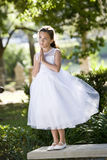 Beautiful child in white dress on park bench. Beautiful child wearing formal white dress posing on park bench stock photo
