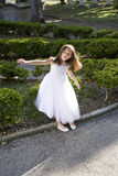 Beautiful child in white dress playing outdoors Royalty Free Stock Photography