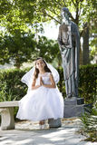Beautiful child in white dress sitting on bench. Beautiful child wearing formal white dress on park bench Stock Images