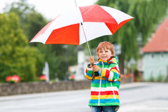 Beautiful child with yellow umbrella and colorful jacket outdoor Stock Photo