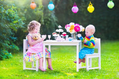 Beautiful children at doll tea party. Two happy children, cute curly toddler girl and a little baby boy, brother and sister, enjoying a tea party with their toys stock photography