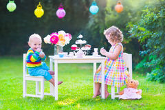 Beautiful children at doll tea party. Two happy children, cute curly toddler girl and a little baby boy, brother and sister, enjoying a tea party with their toys royalty free stock images