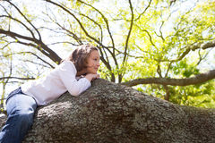 Beautiful children kid girl resting lying on a tree Stock Photo