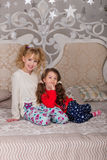 Beautiful children play in their pajamas on the bed before goin. Girls getting ready for bed. Beautiful children play in their pajamas on the bed before going to royalty free stock images