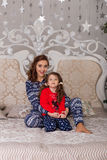 Beautiful children play in their pajamas on the bed before goin. Girls getting ready for bed. Beautiful children play in their pajamas on the bed before going to stock photography