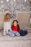 Beautiful children play in their pajamas on the bed before goin. Girls getting ready for bed. Beautiful children play in their pajamas on the bed before going to royalty free stock photos