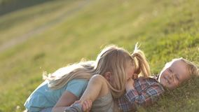 Beautiful children playing on green grassy field. Side view of two playful children having fun on green field in park. Lovely blonde sister in eyeglasses kissing stock video