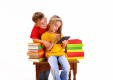 Beautiful children read e-book surrounded by books Stock Photo