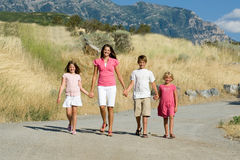 Beautiful children walking in the mountains. A group of four beautiful children smile at the camera while walking, holding hands in the mountains Stock Image