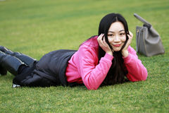 Beautiful china girl Lie on the grass Royalty Free Stock Photography