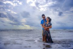 beautiful Chinese Asian couple with woman hug her boyfriend romantic and cuddle on the beach smiling in dating and romance stock image
