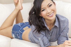 Beautiful Chinese Asian Woman in Denim Shorts. A beautiful young Chinese Asian Oriental woman or girl with a wonderful toothy smile laying down on a sofa wearing Royalty Free Stock Images