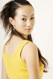 Beautiful Chinese girl. In yellow gilet royalty free stock photo