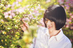 Beautiful chinese girl among flowers Stock Image