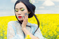 Beautiful Chinese girl in kimono with long false nails with red lipstick in rape Royalty Free Stock Image