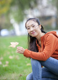 Beautiful Chinese girl picking yellow leaf Stock Images