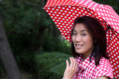 Beautiful Chinese girl smiling with an umbrella. A young beautiful Chinese woman with a dotted umbrella and shirt in Odaiba, Tokyo, Japan, 2009 Royalty Free Stock Photography