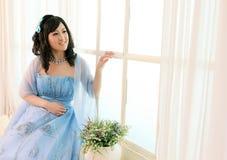 Beautiful Chinese girl standing aside window Royalty Free Stock Image