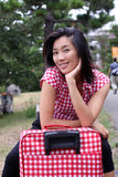 Beautiful Chinese happily waiting on her suitcase Royalty Free Stock Photography