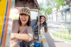 Beautiful Chinese or Japanese woman drive auto rickshaw and her Thai friend is sitting behind her. They are closed friend and royalty free stock photography