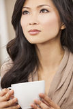 Beautiful Chinese Oriental Asian Woman Drinking Tea or Coffee. A beautiful young Chinese Asian Oriental woman drinking tea or coffee from a white cup Royalty Free Stock Images
