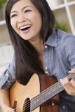 Beautiful Chinese Oriental Woman Smiling & Guitar Stock Image