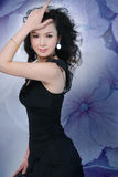 Beautiful Chinese Woman. A beautiful, young Chinese woman in a high fashion pose against a floral background Royalty Free Stock Photo