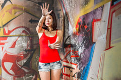 Beautiful Chinese woman by graffiti walls with hands raised Stock Photo