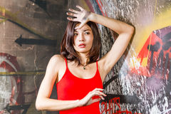 Beautiful Chinese woman by graffiti walls with hands raised Stock Photos