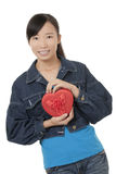 Beautiful Asian woman holding a red heart flirting isolated on a white background Royalty Free Stock Images