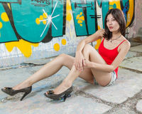 Beautiful Chinese woman sitting by graffiti walls Stock Photography
