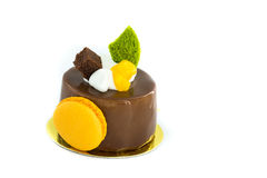 Beautiful chocolate cake with macaroon on the side, siting on golden plate. Stock Image