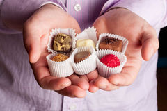 Beautiful chocolate candy in mens palms. Beautiful chocolate candy in palms, close up Royalty Free Stock Photo