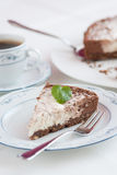 Beautiful chocolate-raw cheese cake ready to eat. With cup of coffee, main focus on mint leaf Royalty Free Stock Images