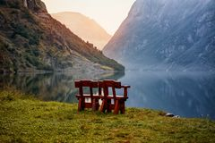 Beautiful choice for unity with nature on the banks of the Norwegian fjord Two chairs to relax in the mountains. Sunrise . stock photos